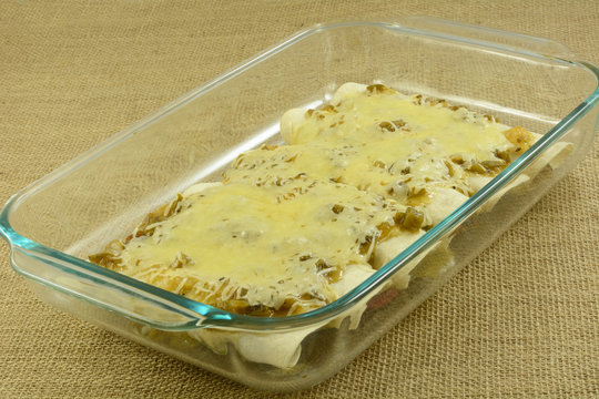Baked chicken and bean enchildas smothered in salsa verde and cheese in glass baking dish