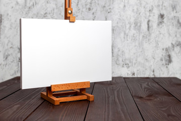 White blank canvas stretched on subframe and an easel standing on a brown wooden table. Mockup
