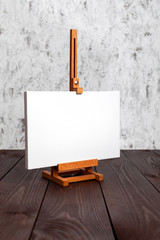 White blank canvas and a wooden easel. Mockup
