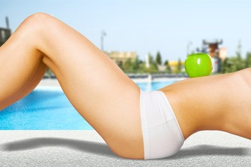 Female body in white underwear with green appple