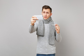 Preoccupied young man in gray sweater, scarf hold thermometer, doing selfie shot on mobile phone, making video call isolated on grey background. Health ill sick disease treatment, cold season concept.