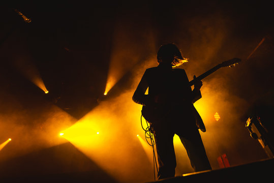Guitarist plays solo. silhouette of guitar player in action on music stage. popular music rock band performs on stage.