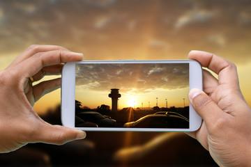 hands with smartphone photographing sunrise and silhouette of cars through the city - Aeroporto Galeão - Rio de Janeiro/Brasil