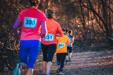 Cross Country race. Female athlete run in autumn forest
