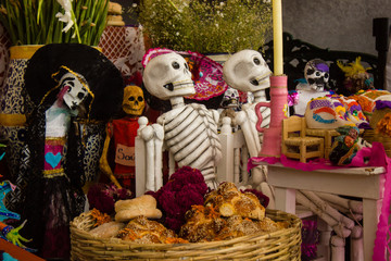 A typical scene of an altar during the day of the dead celebration in mexico with skull candy, handmade baskets, colorful decoration, flowers and candles .
