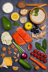Flatlay setting of healthy food: fish salmon, bowl of rice, avocado, fruits and vegetables. Balanced diet, food background