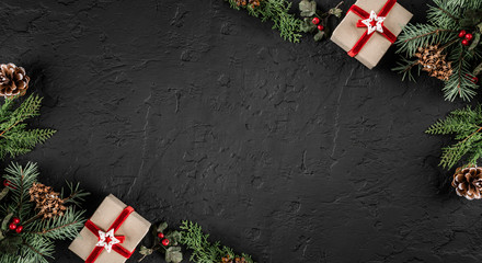 Creative layout frame made of Christmas tree branches, pine cones, gifts on dark background. Xmas and New Year theme., snow. Flat lay, top view, space for text
