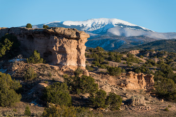 Sandstone red rock formation with the snow-capped peaks of the Sangre de Cristo mountain range in the distance near Santa Fe, New Mexico