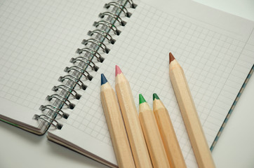 Five colored wooden pencils on the background of a blank sheet of notepad on a spring