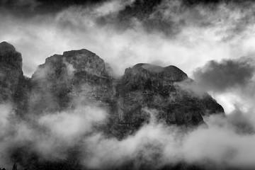 winter scene with rocky mountain peaks inside clouds