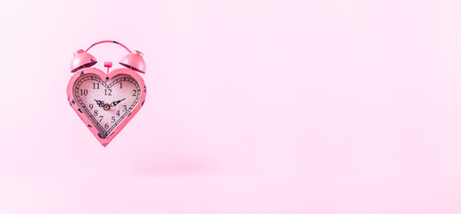 Heart shaped clock on pink background.  Valentines day and love infitity and duration concept