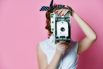 Young pinup style woman take photo use antique old portable photo camera medium frame on light pink
