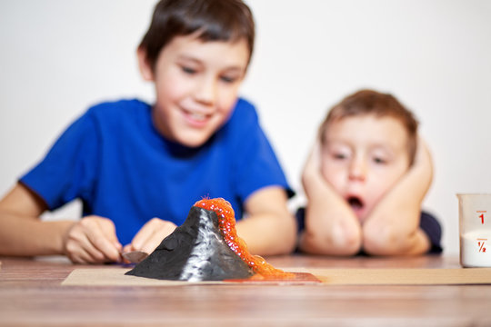 volcanic eruption. school science project. Two boys watching a chemistry experiment. children surprised. Chemical reaction of baking soda and vinegar