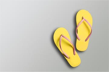 Yellow rubber sandals flip flops on wooden background