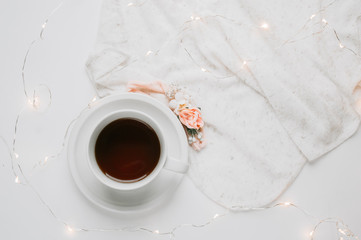 NEUTRAL BACKGROUND WITH FAIRY LIGHTS TEA ON A MUG AND SWEET FLOWERS