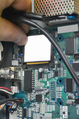 Repair electronic board. Removing Compact Flash Card from electronic board for check and repair. Industry concept.