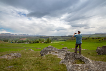 A male tourist takes a photo of the landscape at Elephant Rocks, in the Waitaki Valley, New Zealand, with his  cellphone