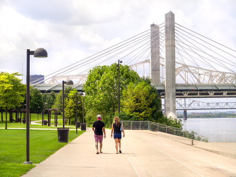 People walk on a path along urban Waterfront Park in Louisville Kentucky