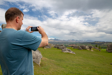 A tourist takes photos on his smartphone while he is sightseeing at the Elephant Rocks in New Zealand