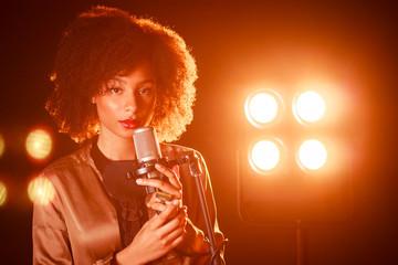Mujer joven con un micrófono en la mano
