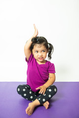 Asian little kid cute child girl practicing yoga exercise with smile and happiness.