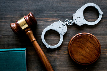 Crime concept. Metal handcuffs near judge gavel and law book on dark wooden background top view
