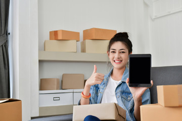 Sme business concept. Young Asian people are packing their packages. Young people are communicating with the phone.