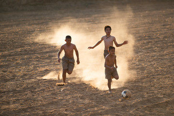 Asian boys friends playing football on the clay ground on summer sunny day. Concept friendship and road to play in the world cup.