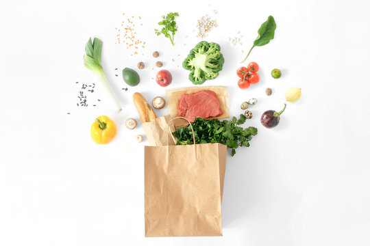 Full paper bag different healthy food white background Top view Flat lay
