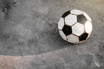 Old football. Black and white soccer ball is placed on the concrete ground.