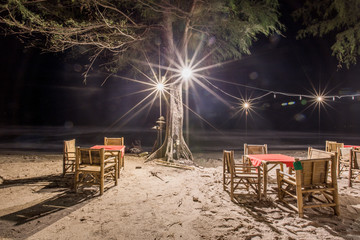The background of light from Beach restaurant at night, with chairs, table to sit, with customer service, during the turbulent sea and continuous rain.