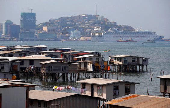 A large cruise ship is docked opposite the stilt house village called Hanuabada, located in Port Moresby Harbour in Papua New Guinea
