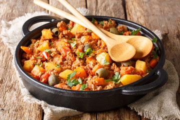 Beef Picadillo cooked with potatoes, carrots, raisins, olives and spices close-up in a frying pan. horizontal