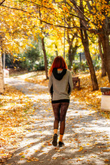 Young Woman Walks in Front of Golden Autumn Leaves