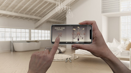 Remote home control system on a digital smart phone tablet. Device with app icons. Interior design of loft open space with bedroom and bathroom with bathtub in the background