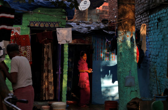 A woman looks on as she prepares to brush her teeth outside her hut on the banks of the river Yamuna in New Delhi