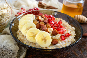 Delicious and healthy oatmeal with banana, pomegranate seeds, almond and cinnamon. Healthy breakfast. Fitness food. Proper nutrition
