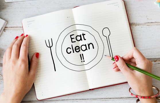 Woman writing Eat clean on a notebook