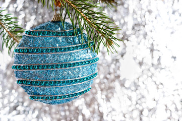 Big beautiful blue ball, green branch of spruce on a light blurred background. Festive greeting card. New Year, Christmas background. Free space for the project