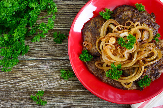 Juicy slices of fried liver and onions on a red plate. Top view.