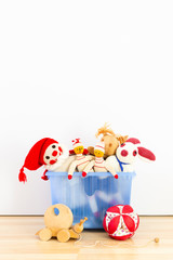 Cute and funny vintage children toys in a blue plastic box in front of a white wall. Assortment consists of a buffoon, a bunny, puppets, a squirrel, a wooden snail and a ball.