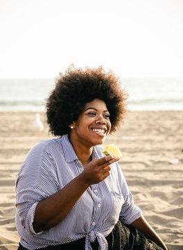 Woman eating a watermelon at a beach picnic
