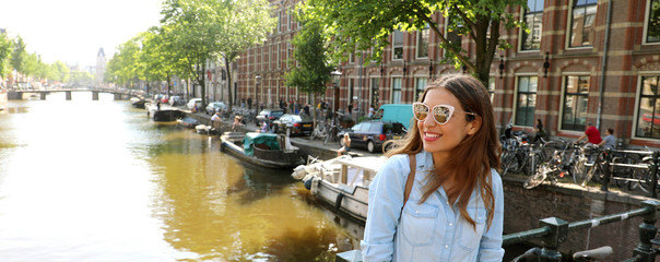 Portrait of beautiful cheerful girl with sunglasses looking to the side on one of typical Amsterdam channels, Netherlands. Panoramic banner view.