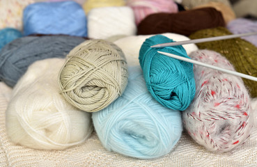 Multicolored knitting spools of wool and thread and knitting needles