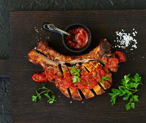Pork chop on the bone with tomato sauce. view from above.