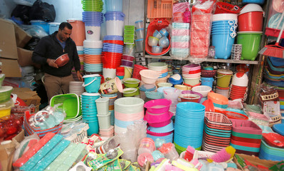 A shop owner sells plastic household items at his shop in Baghdad