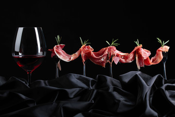 Wall Mural - Prosciutto with rosemary and glass of red wine on a black background.