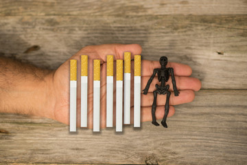 Smoking kills concept suggested by many cigarettes and human skull in hand of a smoker