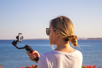 Attractive female records video with modern 3d gimbal stabilized camera smartphone.