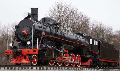 Front side view of old classic black soviet steam locomotive with red star on front